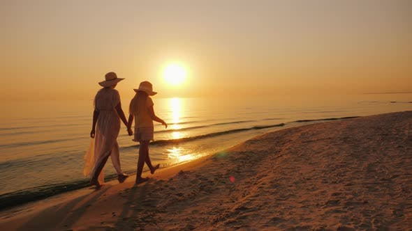 Cover Image for Mom and Daughter Are Walking By the Sea at Sunset