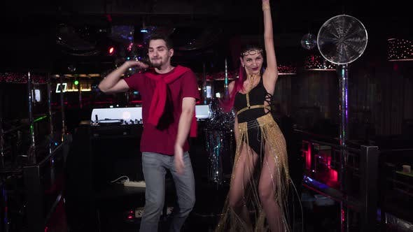 Young Cheerful Man and Woman Dancing on Stage in Night Club. Smiling Male DJ and Female PJ Having