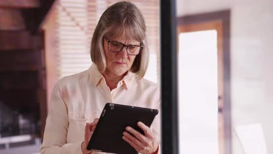 Independent senior woman using tablet device to browse online inside modern home
