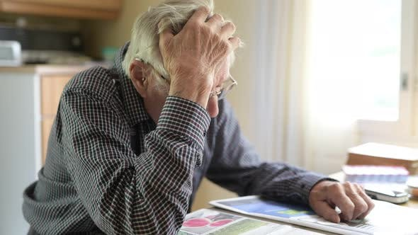 Thumbnail for Senior Man Thinking While Reading Newspaper By The Window