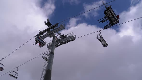 Thumbnail for Ski Lift with Skiers on a Background of Blue Sky and Clouds. Ski Resort