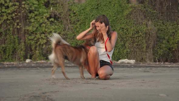 Thumbnail for Young Woman Petting Cute Dog on Ocean Beach