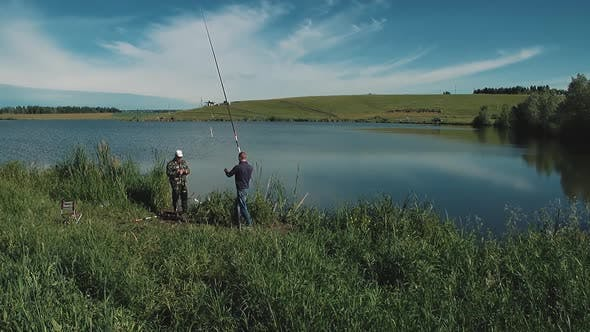Two Young Guys Are Fishing on the Lake