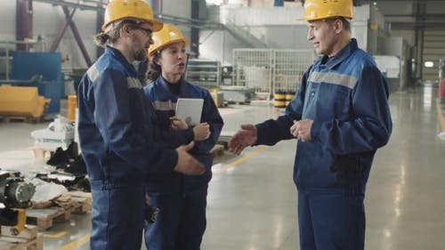 Engineers Shaking Hands At Plant Facility