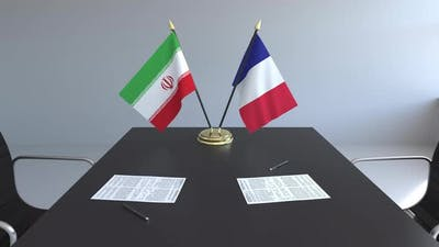 Flags of Iran and France and Papers on the Table