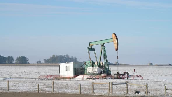 Thumbnail for Oil pumpjack operating in a snowy field on a foggy morning