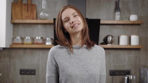 Thumbnail for Charming Young Brunette Woman Is Smiling Standing in a Kitchen in Apartment, Looking at Camera and