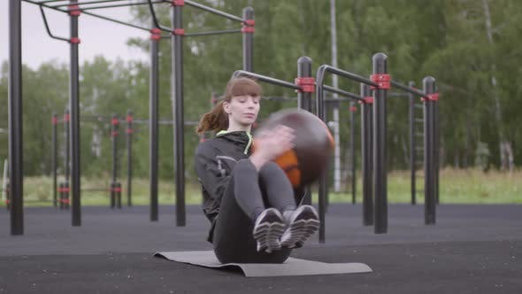 Thumbnail for Woman Doing Medicine Ball Side Twists at Outdoor Workout Court