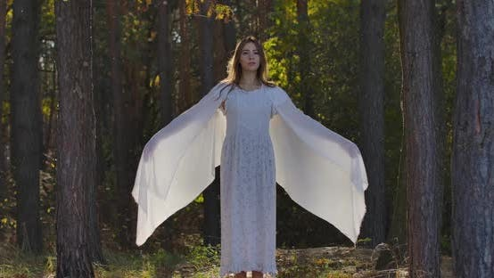 Thumbnail for Smiling Brunette Caucasian Woman Raising Up Hands Wrapped in Light White Shawl and Looking Forward