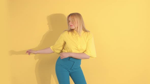 Cover Image for Young Woman in Bright Clothes on Bright Yellow Background in Studio
