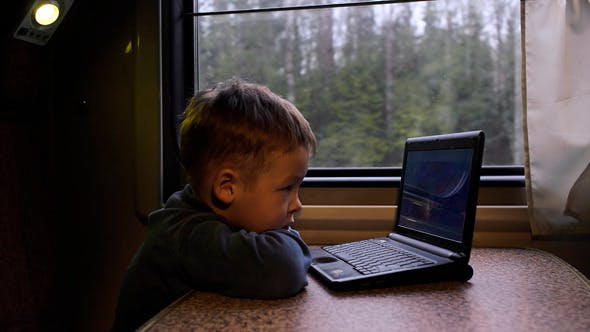 Thumbnail for Little Boy In The Train Watching Video On Laptop
