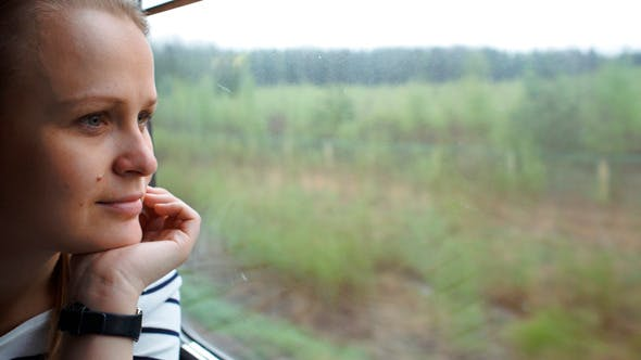 Thumbnail for Young Woman Looking Out The Window Of Moving Train