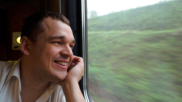 Young Man Having Exciting Phone Talk In The Train