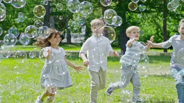Thumbnail for Happy Children Running through Lots of Soap Bubbles