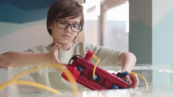 Caucasian Intelligent Boy Experimenting with Robo Boat