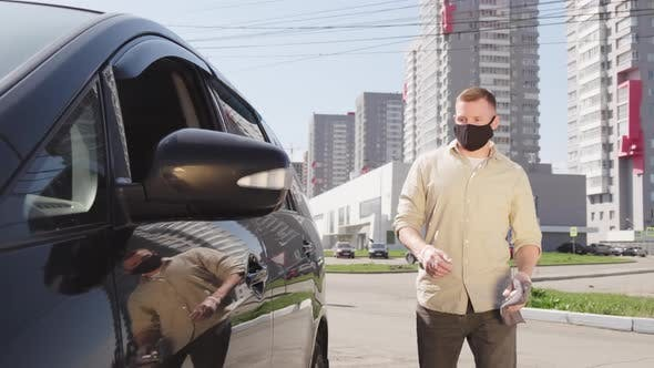 Man in Face Mask Spraying Car Door Handle with Disinfectant