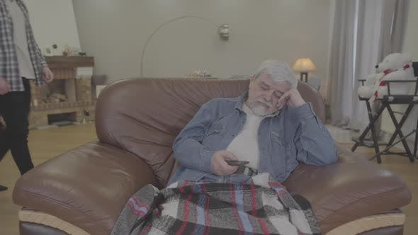 Thumbnail for Portrait of Old Caucasian Man Getting Asleep As Watching TV in the Evening at Home. Adult Son Taking