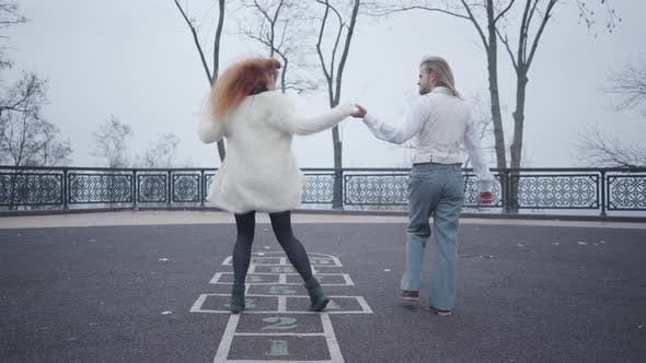Cover Image for Young Caucasian Man in Elegant Clothes Holding His Girlfriend's Hand As She Jumping on the Hopscotch