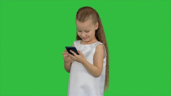 Thumbnail for Little girl using smartphone on a Green Screen, Chroma Key