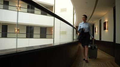Confident Woman Walking Along Inner Hotel Balcony
