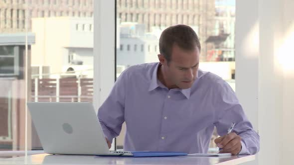 Thumbnail for Businessman using laptop and making notes in office