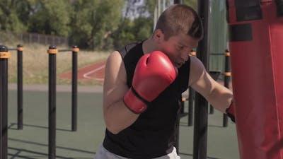 Portrait Of Man Boxing Punch Bag