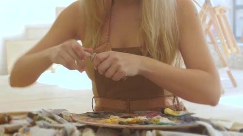 Woman Painter Extrudes on Palette Oil Paints of Different Colors