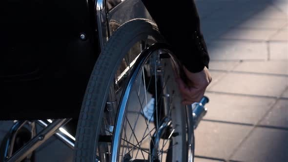 Thumbnail for Rear View of a Man in Wheelchair Near Business Centre with Focus on Hand