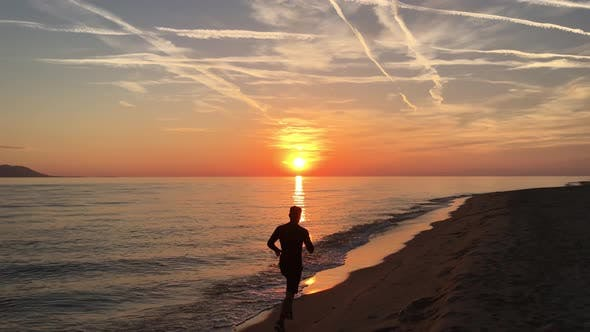Thumbnail for Guy running at the beach during sunset
