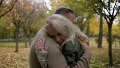 Medium Shot of Married Couple Hugging Gently in Autumn Park