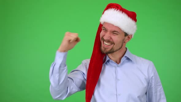 Thumbnail for A Young Handsome Man in a Christmas Hat Celebrates