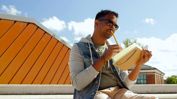 Thumbnail for Indian Man with Notebook or Sketchbook on Roof Top