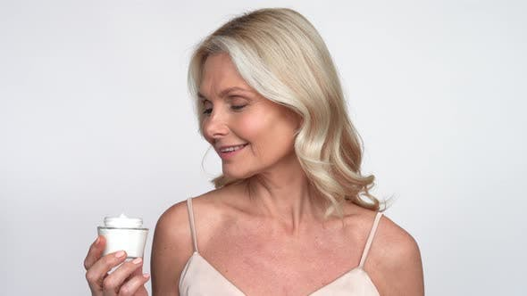 Smiling 50s Middle Aged Woman Putting Facial Cream on Face Looking at Camera