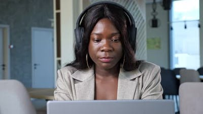 Cheerful Black Woman with Headphones Talks on Videocall