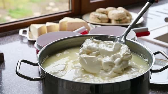 Mischen der Käsemasse in einem Topf bei der Herstellung von hausgemachtem Käse