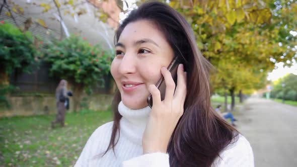 Asian Smling Girl Wearing White Sweater Talking By Smartphone and Walking in Park.