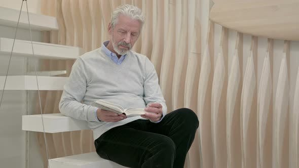 Thumbnail for Old Man Reading Book While Sitting on Staircase