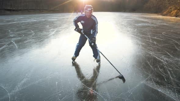 Thumbnail for Eishockeyspieler Training mit Dribbling auf Frozen See, Profi Mann Athlet Outdoor Sonnenuntergang