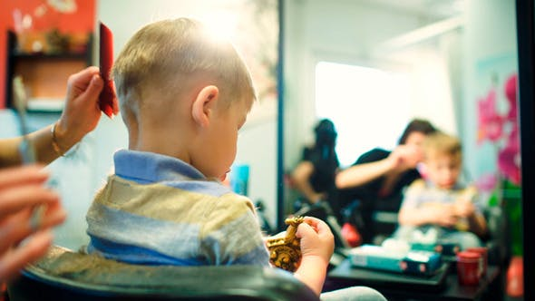 Thumbnail for Hairdresser Cutting Childs Hair While He Playing