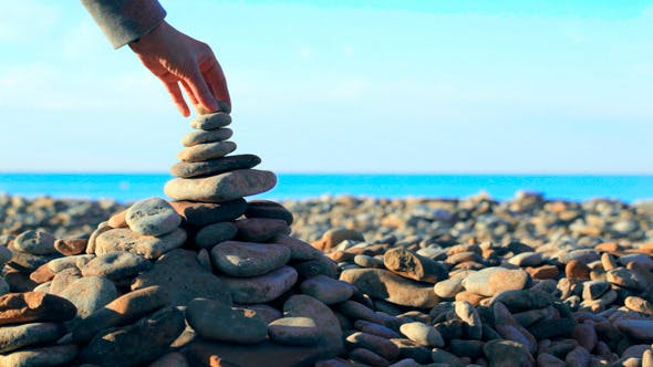 Thumbnail for Hand Putting Last Stone On Pyramid At The Seaside