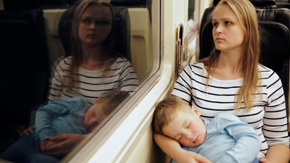 Thumbnail for Tired Woman In The Train With Sleeping Son On Her