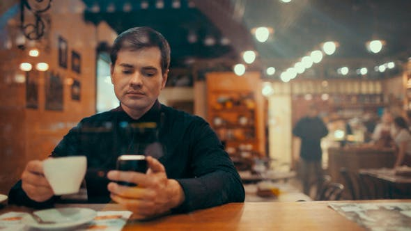 Thumbnail for Young Man Using Phone And Having Coffee In A Cafe