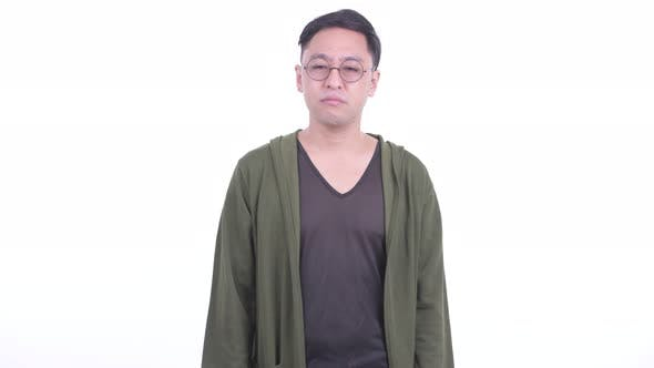Thumbnail for Sad Japanese Man with Eyeglasses Giving Thumbs Down