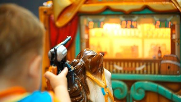 Thumbnail for Junge Reiten ein Spielzeug Pferd und Schießen mit Spielzeugpistole
