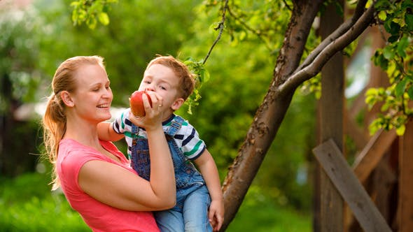 Thumbnail for Mother Feeding Her Son With An Apple In The Garden