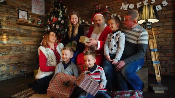Thumbnail for Santa Claus Gives New Year Gifts To Big Family in Decorated Room for Christmas with Tree