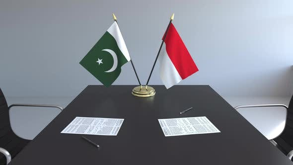 Flags of Pakistan and Indonesia and Papers on the Table