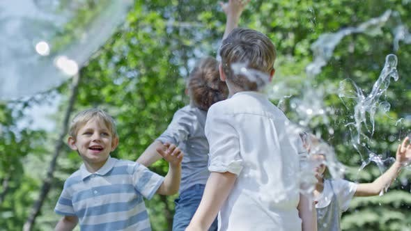 Cover Image for Exhilarated Kids Catching Bubbles in Park