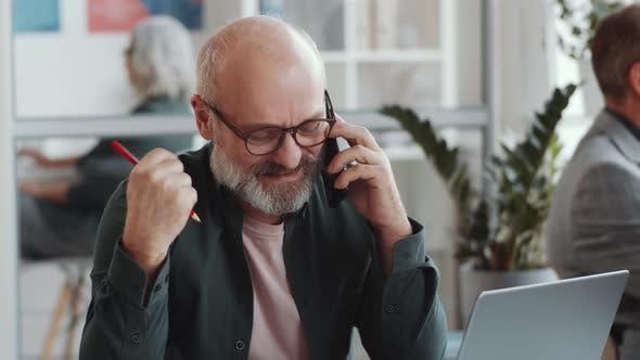 Thumbnail for Senior Man spricht am Telefon, mit Laptop und Notizen am Schreibtisch machen