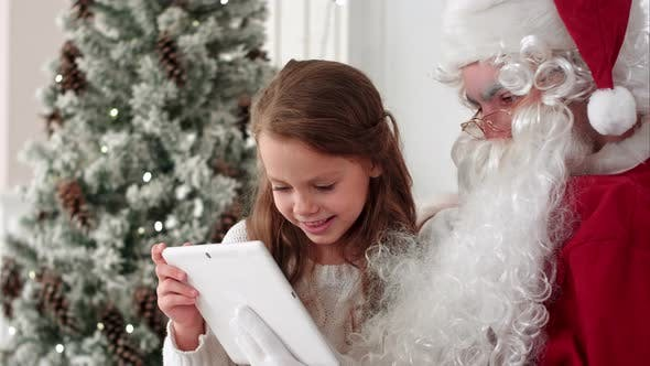 Thumbnail for Santa Claus and Happy Little Girl Taking Selfies Wth Tablet Sitting in an Armchair Next To the